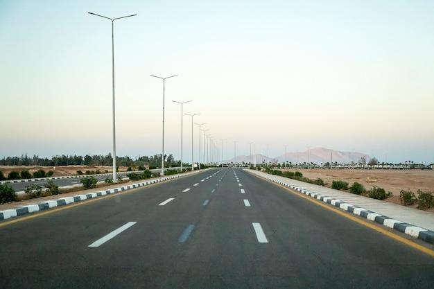 Route asphaltée dans le désert égyptien dans la lumière du soir.