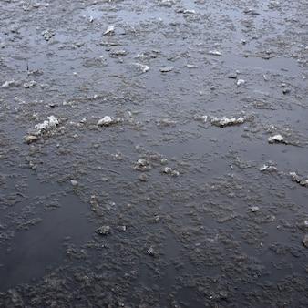 Route asphaltée endommagée avec des nids de poule, rempli d'eau avec de la glace