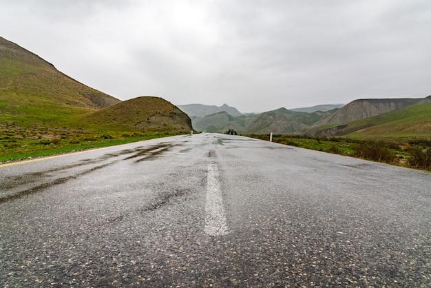 Route asphaltée humide en zone montagneuse