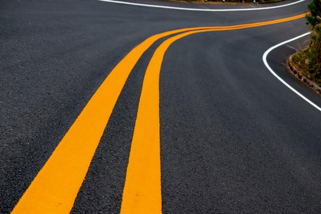 Route asphaltée, lignes de circulation jaunes et blanches