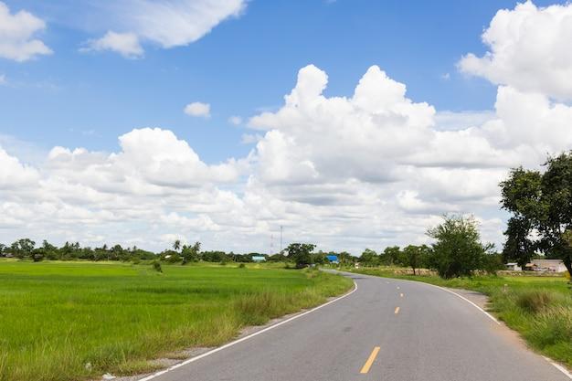 Route asphaltée et nuages sur ciel bleu