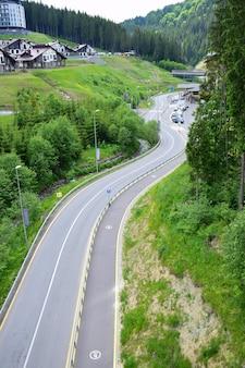 Route asphaltée sinueuse vide dans une station de ski en été. vue sous un angle élevé. en arrière-plan il y a de belles maisons de vacances