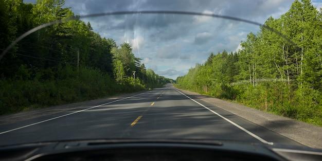 Route au milieu des arbres vu à travers le pare-brise de la voiture, doaktown, nouveau-brunswick, canada