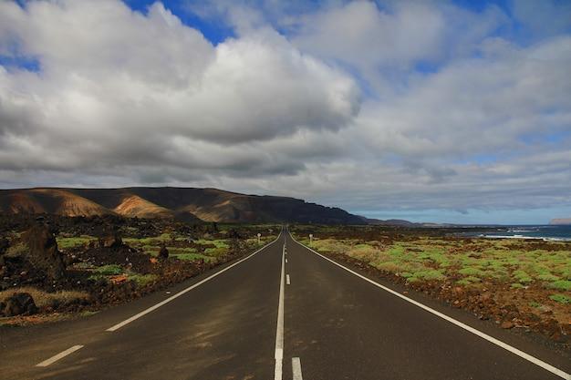 Route au milieu d'un champ herbeux avec une montagne au loin sous un ciel nuageux