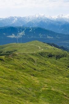 Route au sommet de la montagne serpente le long de la plaine verte sur fond de montagnes bleues et de nuages