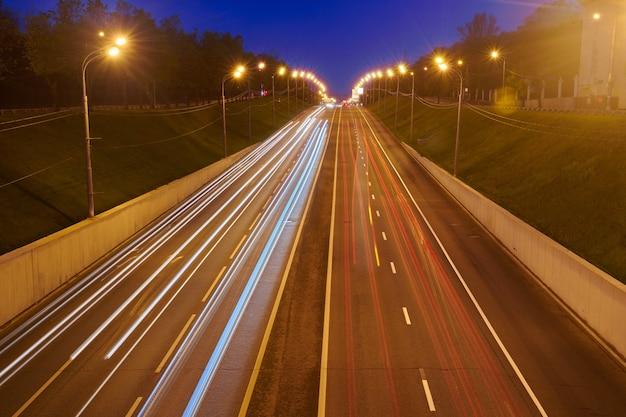 Route d'autoroute de nuit avec des lumières de voitures. sentier de feu jaune et rouge sur la route avec trafic de vitesse. fond urbain abstrait longue exposition