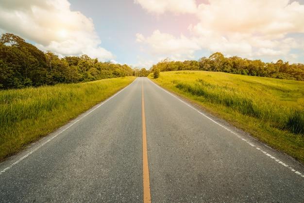Route de l'autoroute à travers l'herbe verte sous le ciel bleu.