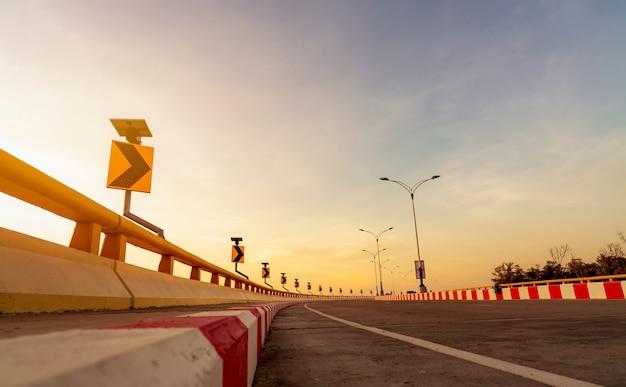 Route en béton courbe avec panneau de signalisation courbe et panneau d'arrêt interdit rouge-blanc
