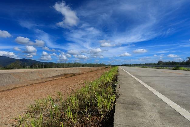 Route en béton et le sol parallèles les uns aux autres avec un beau ciel au-dessus.