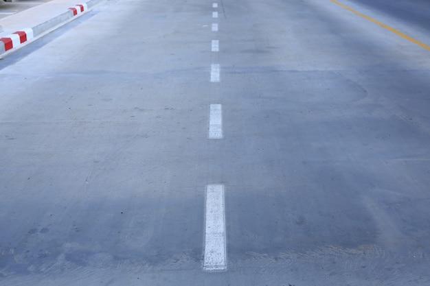 Route en béton avec une voie de marquage blanc.