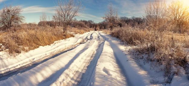 Route de campagne couverte de neige au coucher du soleil dans la forêt d'hiver. panorama