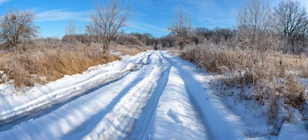 Route de campagne couverte de neige dans la forêt en hiver. panorama