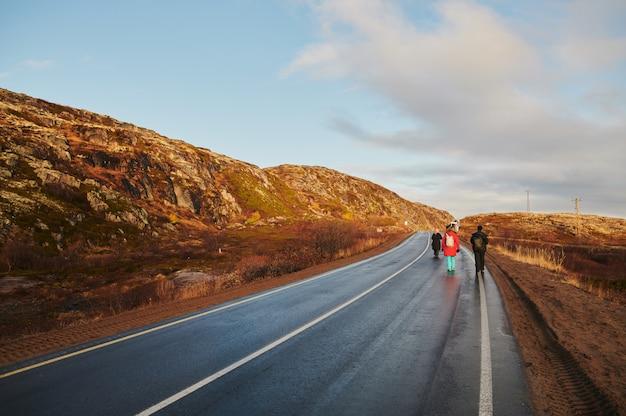 Route de campagne du nord parmi les collines avec des arbres et des buissons de toundra d'automne colorés sur une journée nuageuse.