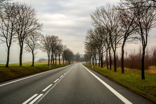 Route de campagne incurvée à deux voies serpentant à travers les arbres.