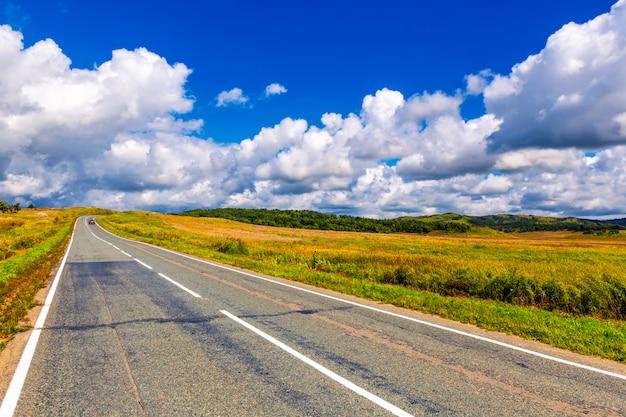 Route de campagne sinueuse et ciel bleu nuageux