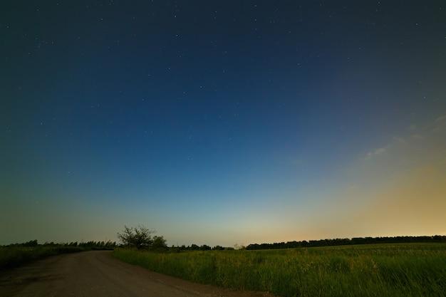Route de campagne sur une surface du ciel étoilé