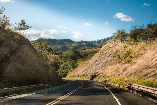 Route avec ciel bleu montagnes et nuages