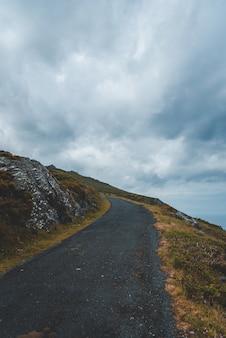 Route sur la colline avec personne ne marchant sous le ciel nuageux