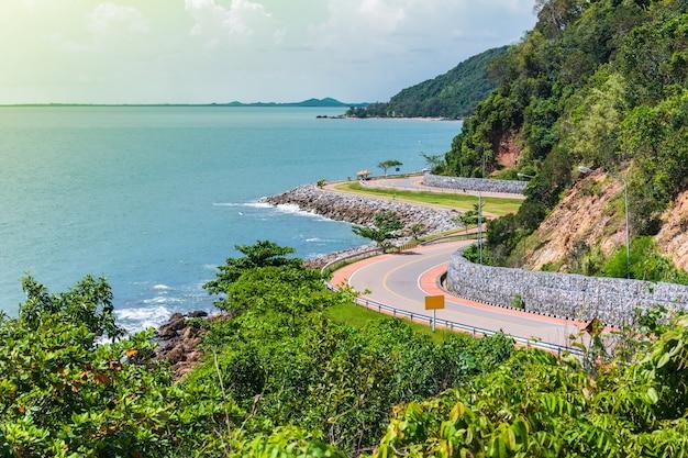 Route à côté de l'océan et de la montagne sous le ciel bleu