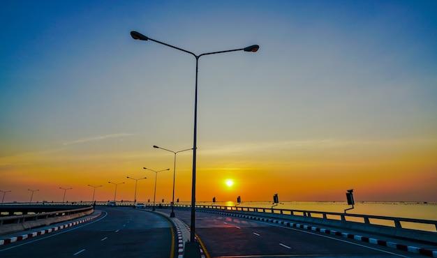 Route côtière incurvée avec lampadaire au coucher du soleil
