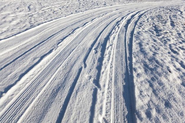 Route couverte de neige dans le champ, dirigée vers la gauche. période hivernale de l'année, des traces de pneus de voiture sont visibles sur la neige.