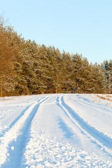 Route couverte de neige en hiver, a la surface des congères, des traces des voitures passées sont visibles, forêt et ciel bleu