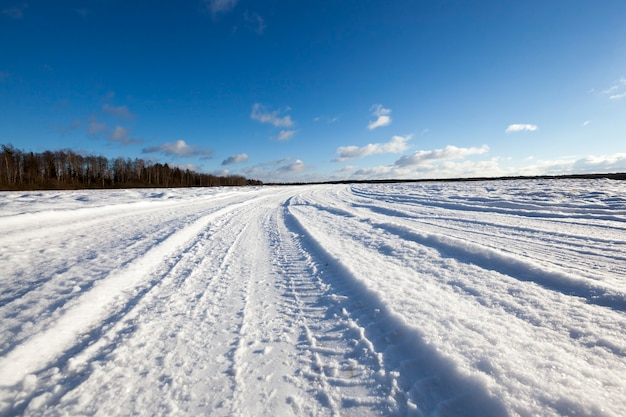 Route couverte de neige en hiver. traces visibles de la voiture. ciel en arrière-plan