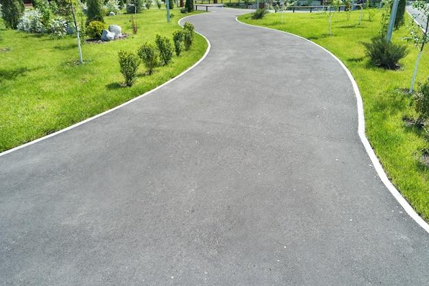 Route cyclable dans le parc verdoyant avec de l'herbe verte