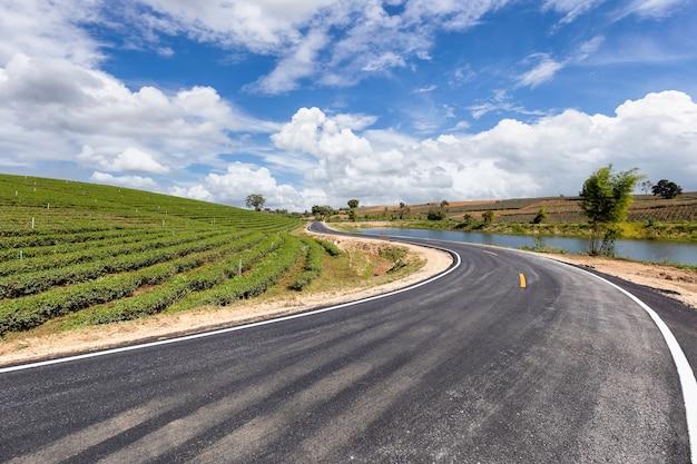 Route dans un beau paysage d'un champ et de nuages sur un ciel bleu