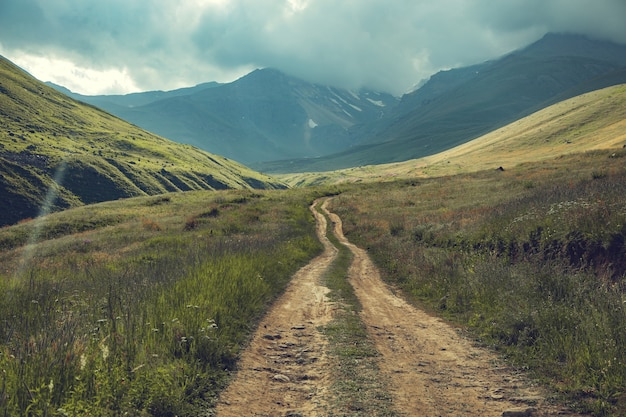 Route dans la montagne sous un ciel sombre