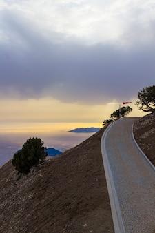 Route dans les montagnes avec coucher de soleil jaune et mer