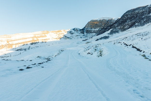 Route dans les montagnes couvertes de neige, montagnes d'hiver
