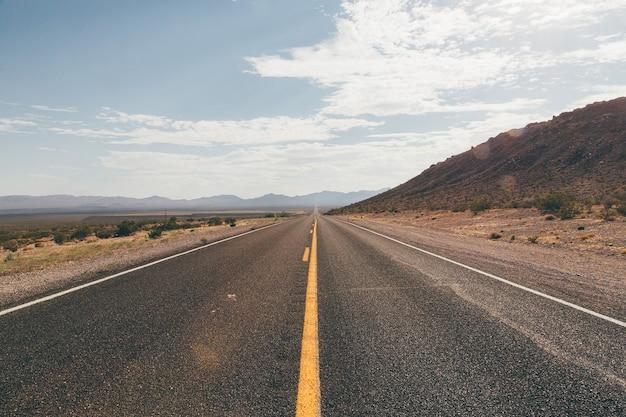 Route droite dans le parc national de death valley sur fond de jour nuageux