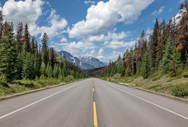 Une route droite à travers death valley, californie, autoroute au coucher du soleil