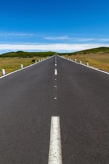 Une route droite sur la zone avec un ciel bleu et des nuages au loin