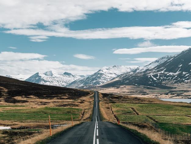 Route entourée de collines couvertes de verdure et de neige sous un ciel nuageux en islande