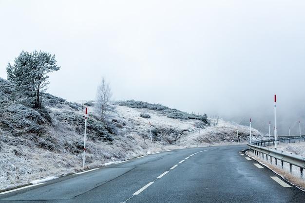 Route entourée de montagnes enneigées couvertes de brouillard