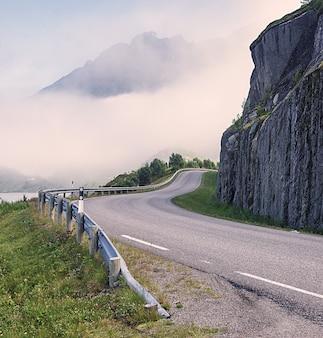 La route est pliée autour de la falaise contre les montagnes, norvège
