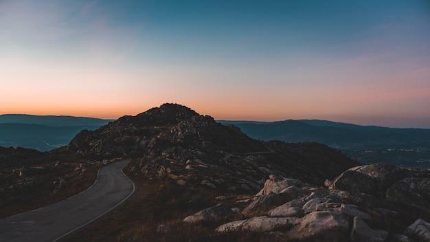 Route étroite menant à une grotte rocheuse sous le beau ciel coucher de soleil