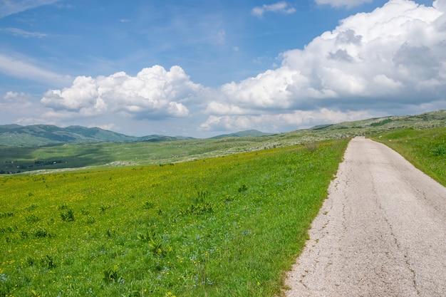 Une route étroite et sinueuse traverse des prés et des montagnes pittoresques.