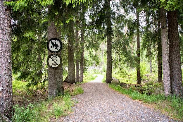 Route en forêt avec un signe de non-équitation et un signe de non-véhicules