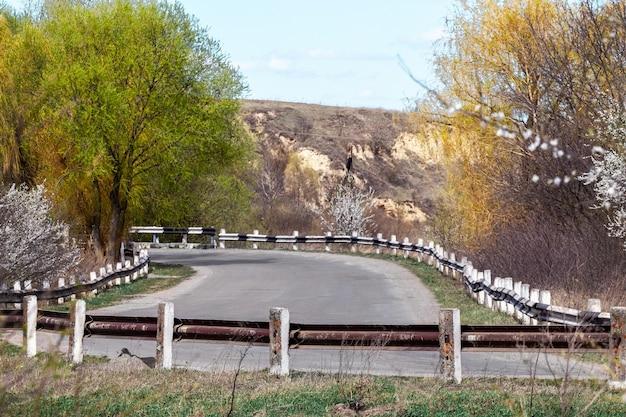 Route goudronnée avec clôture en fer à la campagne