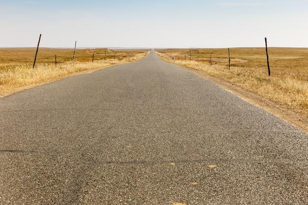 Route goudronnée dans la steppe avec éoliennes à l'horizon, mongolie intérieure
