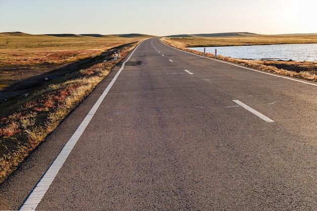 Route goudronnée dans la steppe mongole au bord d'un petit lac