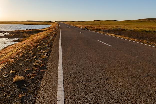 Route goudronnée dans la steppe mongole le long d'un petit lac