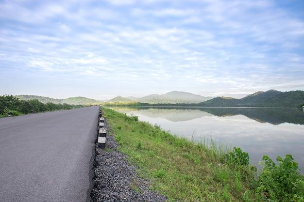 Route goudronnée avec réservoir sur ciel bleu et montagnes