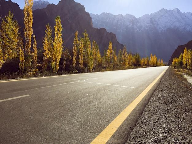 Une route goudronnée vide sur l'autoroute du karakoram contre la chaîne de montagnes enneigée en automne.