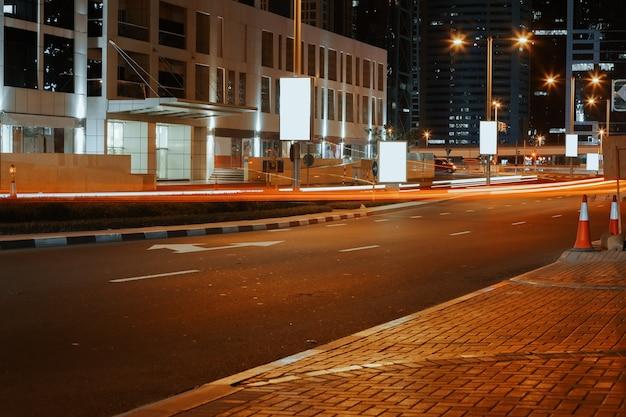 Route goudronnée vide avec des bâtiments modernes la nuit à dubaï