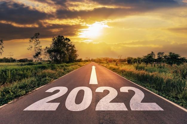 Route goudronnée vide et concept de nouvel an 2022. conduire sur une route vide vers les objectifs 2022 avec le coucher du soleil.