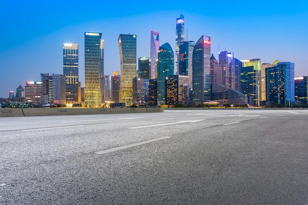 La route goudronnée vide est construite le long des bâtiments commerciaux modernes dans les villes chinoises.